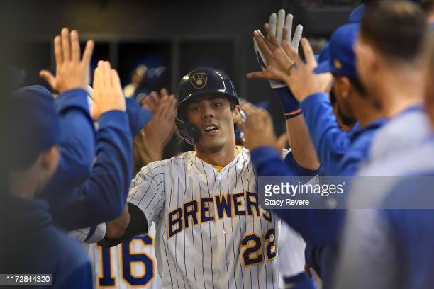 Christian Yelich of the Milwaukee Brewers is congratulated by teammates following a three run home run against the Chicago Cubs during the third...