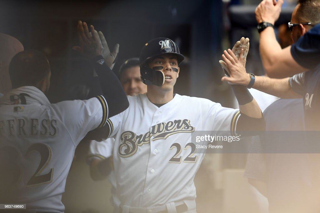 Christian Yelich #22 of the Milwaukee Brewers is congratulated by teammates following a home run during the seventh inning of a game against the St. Louis Cardinals at Miller Park on May 30, 2018 in Milwaukee, Wisconsin.