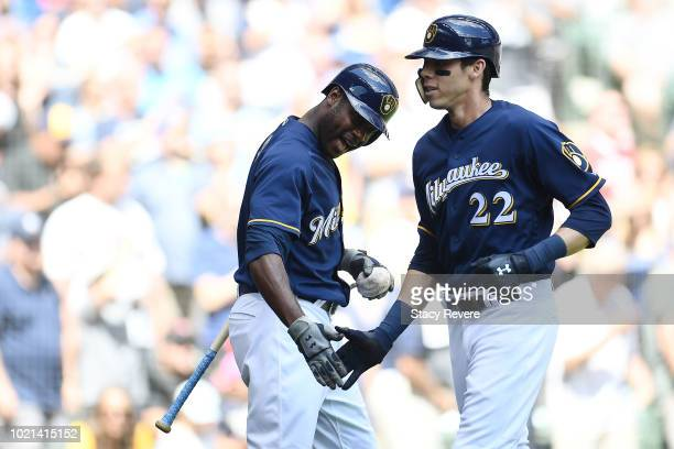 Christian Yelich of the Milwaukee Brewers is congratulated by Lorenzo Cain following a home run against the Cincinnati Reds during the first inning...