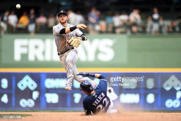 Christian Yelich of the Milwaukee Brewers is forced out at second base as Trevor Story of the Colorado Rockies turns a double play during the tenth...