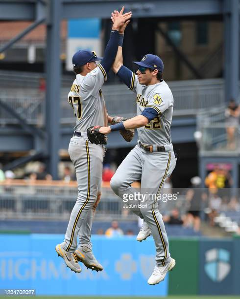 Christian Yelich of the Milwaukee Brewers jumps to give a high five to Willy Adames after the final out in a 2-1 win over the Pittsburgh Pirates...