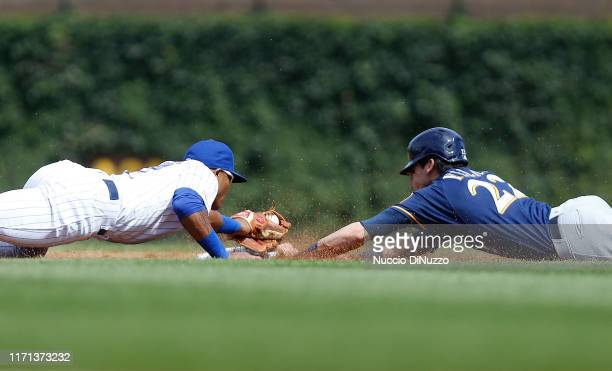 Christian Yelich of the Milwaukee Brewers steals second base in front of Addison Russell of the Chicago Cubs during the third inning of a game at...