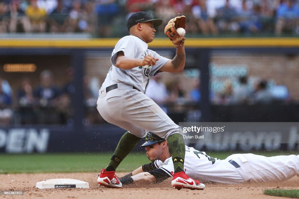 Christian Yelich #22 of the Milwaukee Brewers steals second base past Yairo Munoz #34 of the St. Louis Cardinals in the seventh inning at Miller Park on May 28, 2018 in Milwaukee, Wisconsin. MLB players across the league are wearing special uniforms to commemorate Memorial Day.