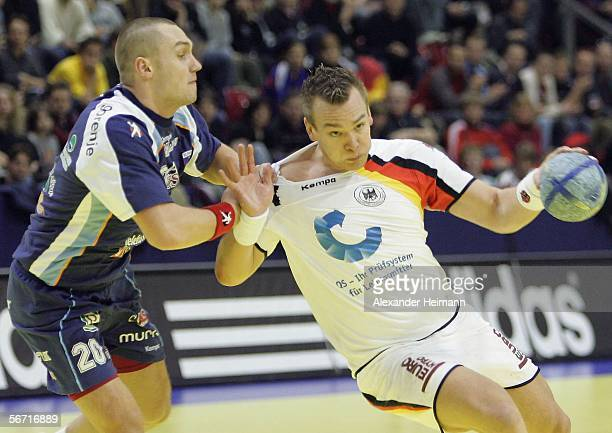 Christian Zeitz of Germany competes with Luka Zvizej of Slovenia during the Handball Euro06 main round match between Slovenia and Germany on February...