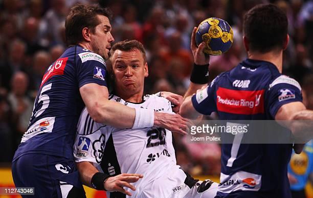 Christian Zeitz of Kiel is challenged by Gillaume Gille and Matthias Flohr of Hamburg during the Toyota Handball Bundesliga match between THW Kiel...