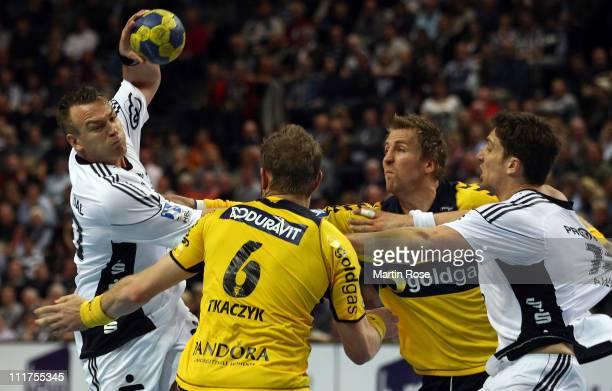 Christian Zeitz of Kiel is challenged by Grzegorz Tkaczyk and Oliver Roggisch of RheinNeckar during the Toyota Handball Bundesliga match between THW...
