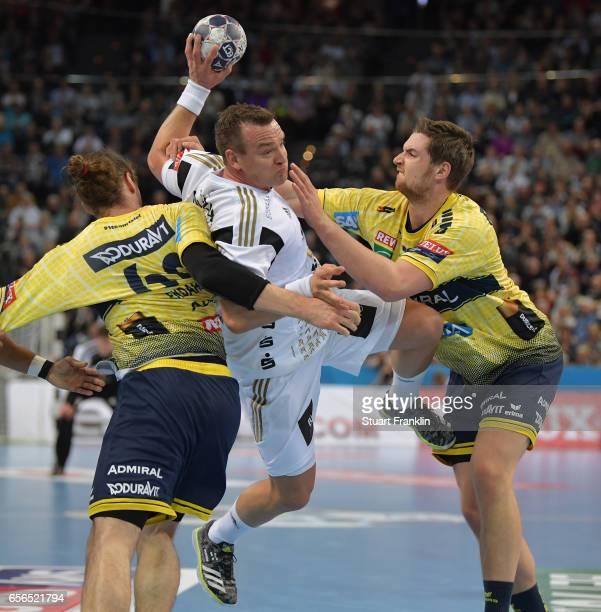Christian Zeitz of Kiel is challenged by Hendrik Pekeler and Kim Ekdahl Du Rietz of Rhein Neckar during the first leg round of 16 EHF Champions...