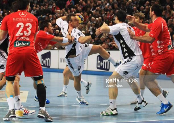 Christian Zeitz of Kiel is challenged by Nenad Vuckovic of Melsungen during the Toyota Handball Bundesliga match between THW Kiel and MT Melsungen at...