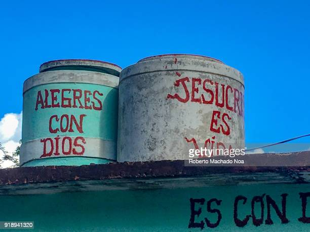 Christianity in Cuba 'Happy with God' and 'Jesus is Life' signs written on water tanks on top of a house