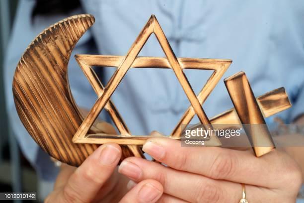 Christianity Islam Judaism 3 monotheistic religions Jewish Star Cross and Crescent Interreligious symbols in hands