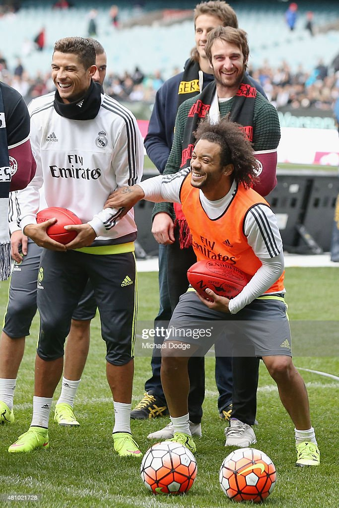 Christiano Ronaldo (L) and Marcelo of Real Madrid react while holding an AFL football during a Real Madrid training session at Melbourne Cricket Ground on July 17, 2015 in Melbourne, Australia.