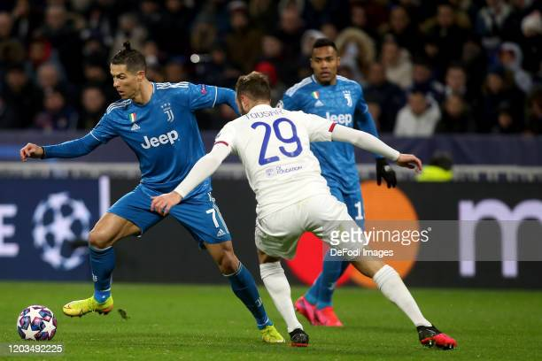 Christiano Ronaldo of Juventus and Lucas Tousart of Olympique Lyon battle for the ball during the UEFA Champions League round of 16 first leg match...