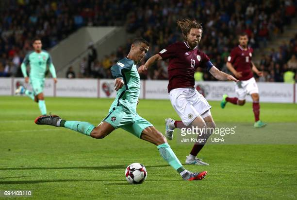 Christiano Ronaldo of Portugal takes a shot at goal under pressure from Kaspars Gorkss of Latvia during the FIFA 2018 World Cup Qualifier between...