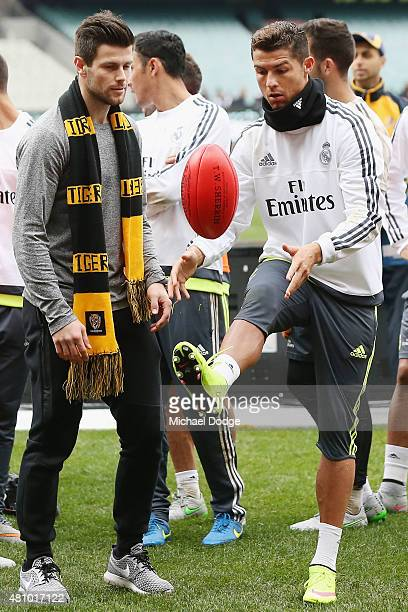 Christiano Ronaldo of Real Madrid kicks an AFL football next to Trent Cotchin of the Richmond Tigers during a Real Madrid training session at...
