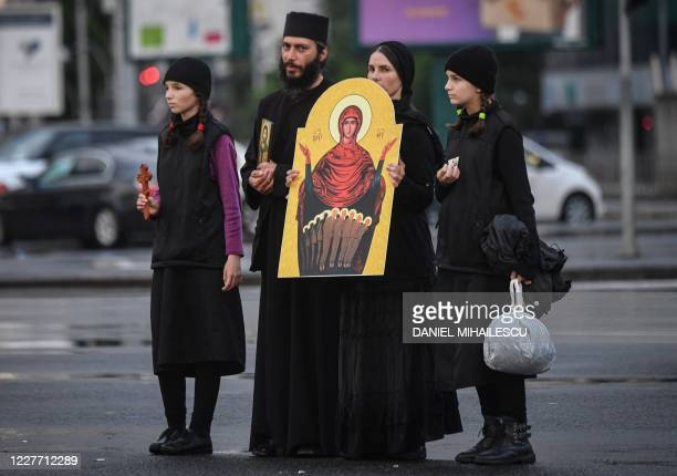 """Christian-orthodox family holds an icon during a protest against the newly adopted """"law of quarantine"""" in front of the Romanian Government..."""