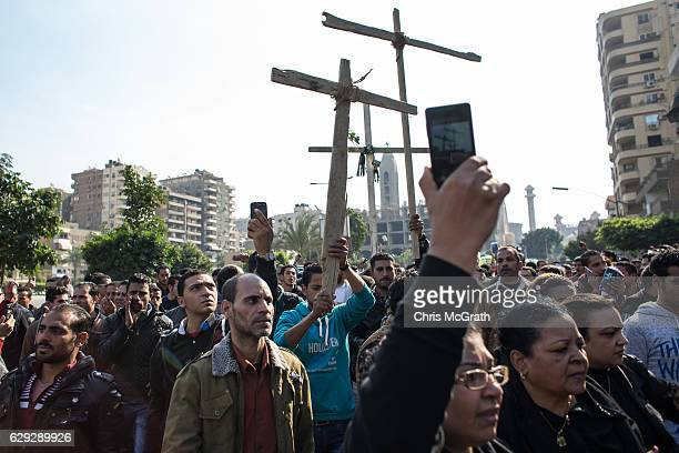 Christians chant slogans and sing as they walk in front of the ambulances carrying the bodies of the victims of yesterdays St Peter and St Paul...