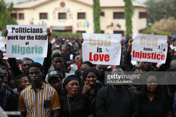 Christians faithfuls hold signs as they march on the streets of Abuja during a prayer and penance for peace and security in Nigeria in Abuja on March...