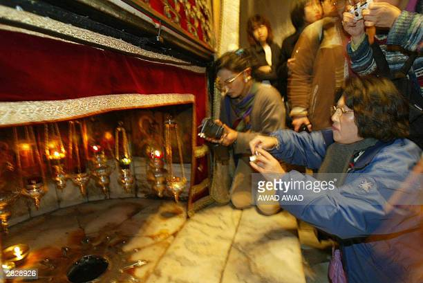 Christians gather at the Grotto the alleged birth place of Jesus Christ in the Church of the Nativity in the West Bank town of Bethlehem 23 December...