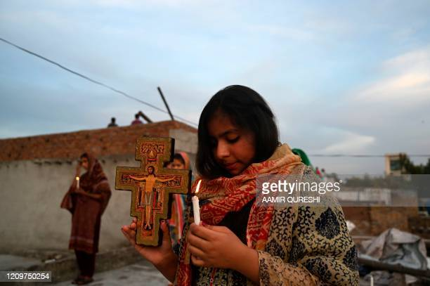 Christians hold candles as they offer prayers during an Easter service in the rooftop of their house during a governmentimposed nationwide lockdown...
