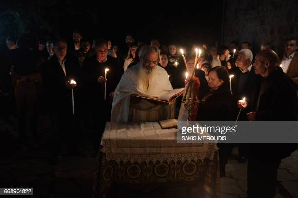 Christians Orthodox worshippers hold candles as they gather for the Orthodox Easter ceremony at the Church of Profitis Ilias at Aimilianos a village...