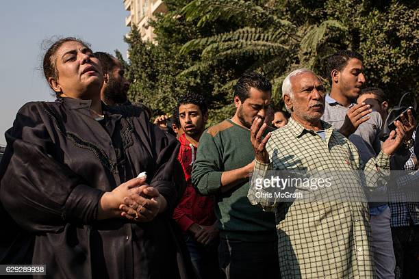 Christians pray in the street outside the orthodox church of the Virgin Mary during the official funerals for victims of yesterdays St Peter and St...