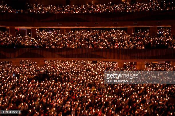 Christians rise candles during a Christmas Eve prayer at a church in Surabaya, East Java, on December 24, 2019.