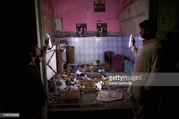 Christians survey the contents of their hair salon on July 23 2010 that was damaged in the on July 19 attacks in the Christian neighbourhood of...