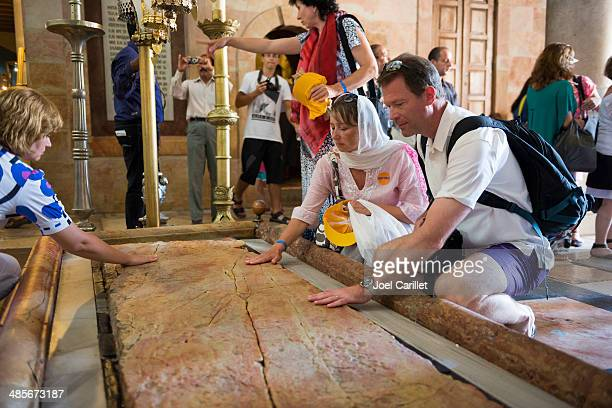 christian pilgrims in jerusalem touch the stone of anointing - historical palestine stock pictures, royalty-free photos & images