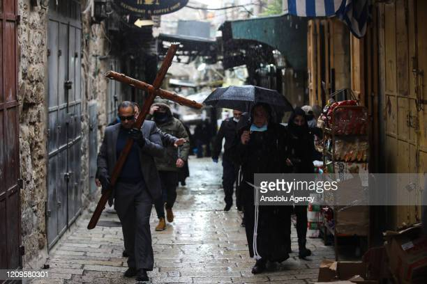 Christians walk along Via Dolorosa on quiet Good Friday due to the restrictions on public gatherings amid the coronavirus in Jerusalem on April 10,...