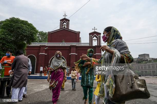 Christians wearing facemasks come out from the Mary Immaculate Church after attending the Sunday prayers in Lahore on June 7, 2020.