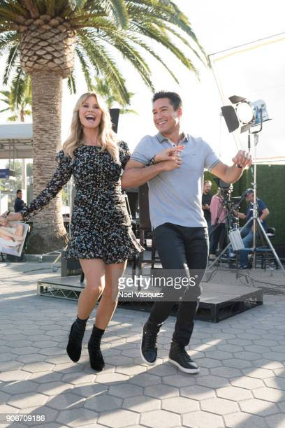 Christie Brinkley dances with Mario Lopez at 'Extra' at Universal Studios Hollywood on January 18 2018 in Universal City California