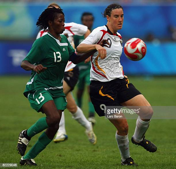 Christie George of Nigeria challenges Birgit Prinz of Germany for the ball during the Women's First Round Group F match between Nigeria and Germany...