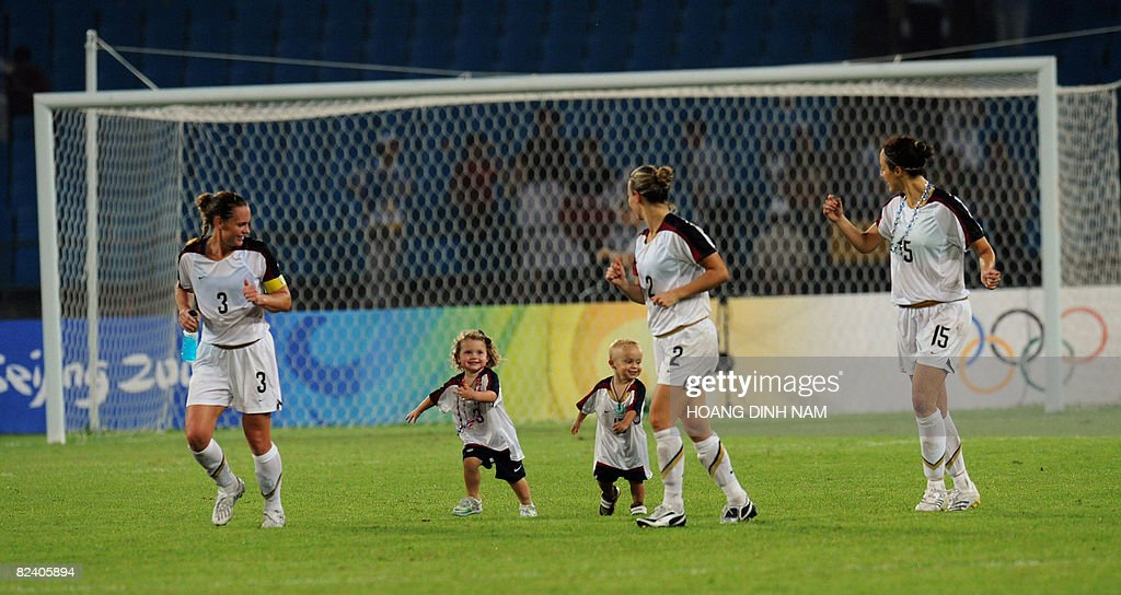 Christie Rampone (L) and Kate Markgraf (R) walk on the pitch with their respective children, daughter Rylie (Romone), (2nd L) and son Keegan (Markgraf) (3rd R) after their team won the Beijing 2008 Olympic Games women's semi-final match against Japan on August 18, 2008. The US won 4-2. AFP PHOTO/HOANG Dinh Nam.