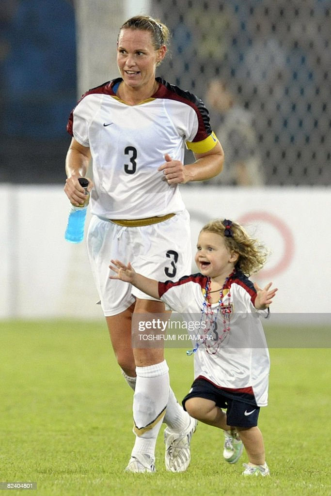 US Christie Rampone (L) runs with her daughter Riley as she celebrates her team's victory over Japan in the 2008 Beijing Olympic Games women's football semi-final match USA vs. Japan, on August 18, 2008 at the workers' stadium in Beijing. USA won by 4-2.
