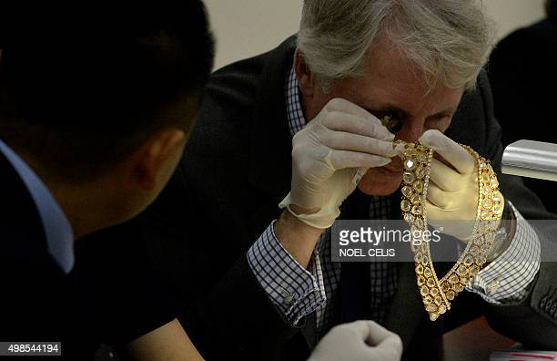 Christie's and Sotheby's auction house appraiser David Warren examines diamond jewellery seized by the Philippine government from former first lady...