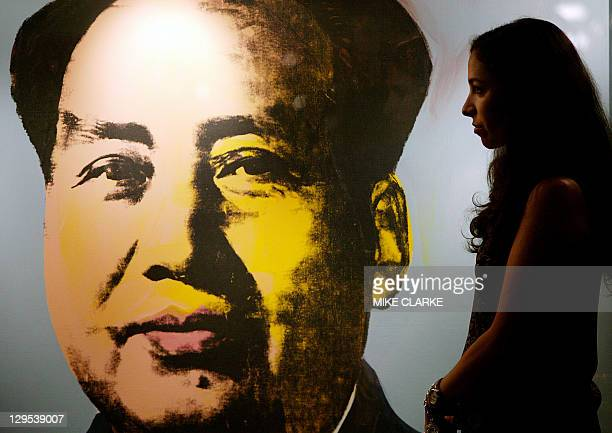 A Christies art expert looks at a portrait by Andy Warhol's 'Mao' with an estimated price of 812 Million USD on display at a press preview in Hong...