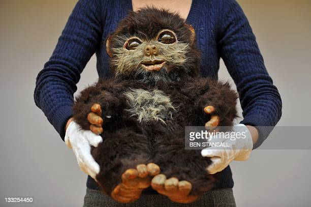 A Christie's auction house employee poses for pictures with a baby Ewok puppet 'Nippett' as featured in 'Star Wars Episode VI Return of the Jedi'...