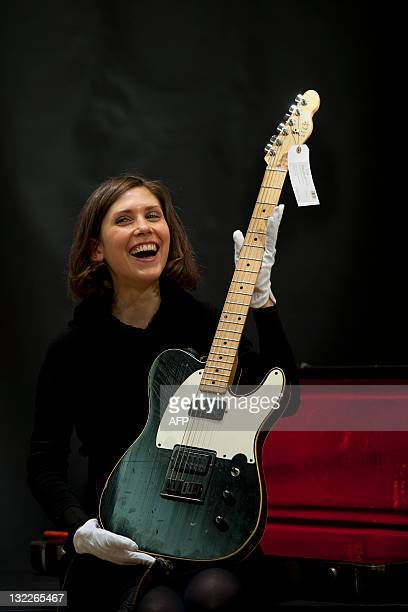 A Christies employ poses with a guitar played at Wembley in 1985 during a Live Aid performance by British rock guitarist Pete Townshend that is...