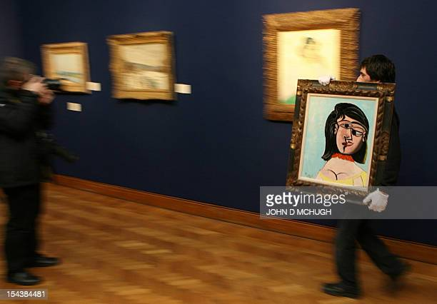 A Christie's employee carries a painting entitled 'Tete de Femme' by Pablo Picasso past a painting by Van Gogh entitled 'L'Arlesienne Madame Ginoux'...