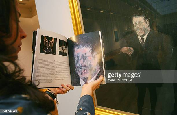 A Christie's employee holds a catalogue in front of painting entitled 'Man in Blue VI' by artist Francis Bacon at Christie's auction house in London...
