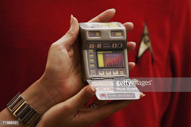 Christies employee holds up a tricorder infront of a replica Star Trek uniform on August 2 2006 in London Christie's New York are marking the 40th...