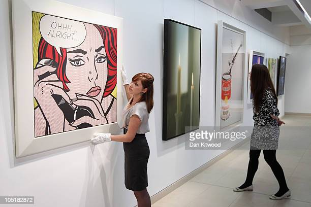 Christie's employee poses next to a piece of work entitled 'OhhhAlright' by Roy Lichtenstein at Christie's auction house on October 11 2010 in London...