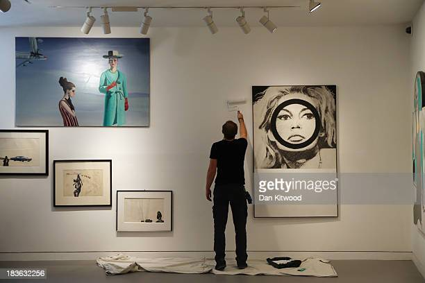 Christie's employee puts the finishing touches to the 'When Britain went Pop' exhibition besides a piece of work entitled 'Bridget Bardot' by Gerald...
