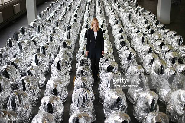 Christie's employee stands amongst Kader Attia's aluminium foil sculptures entitled 'Ghost' at The Thinking Big auction exhibition at the Sorting...