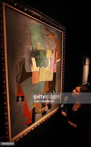 Christie's employee stands in front of Picasso's 'Instruments de musique sur un gueridon 191415' and Mondrian's 'Composition avec bleu rouge jaunne...