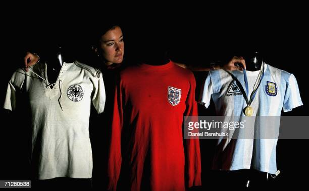 Christies employee Zoe Scoon adjusts past World Cup shirts from West Germany England and Argentina at Christies Auction House on June 23 2006 in...