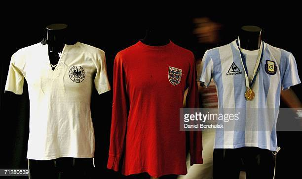 Christies employee Zoe Scoon walks behind past World Cup shirts from West Germany England and Argentina at Christies Auction House on June 23 2006 in...