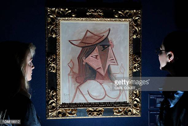 Christie's employees hold a painting entitled 'Tete de femme au chapeau' by Spanish artist Pablo Picasso at Christie's auction house in central...