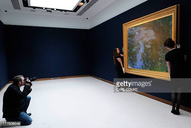 Christie's employees pose for photographs with a painting entitled 'Nympheas' by French artist Claude Monet at Christie's auction house in central...