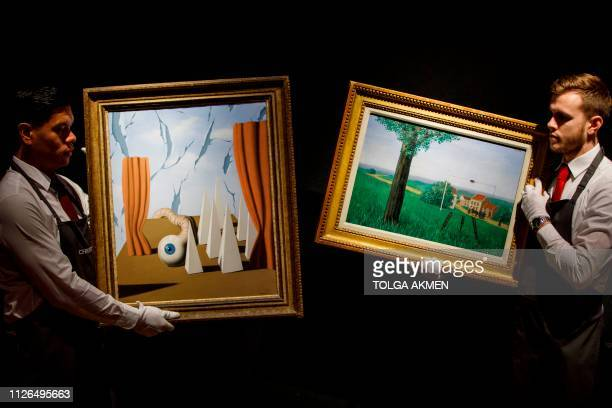 Christie's employees pose with the paintings 'Le monde poetique II' and 'La belle captive' by Belgian Surrealist artist Rene Magritte at a photocall...
